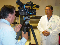 Photo of Dr. Raul Coimbra explainsing the role of UC San Diego Medical Center's trauma team to 10News reporter Bob Lawrence.
