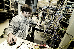 Photo of Calit2 research scientist Nikola Alic with optical  test equipment in the UC San Diego lab