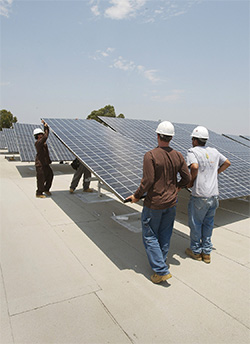 Photo of workers install solar photovoltaic panels on a  building at UC San Diego