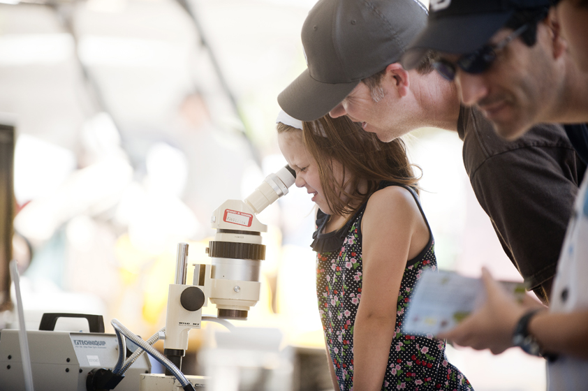 A young visitor looks at a microscope at a Scripps Institution of Oceanography booth.
