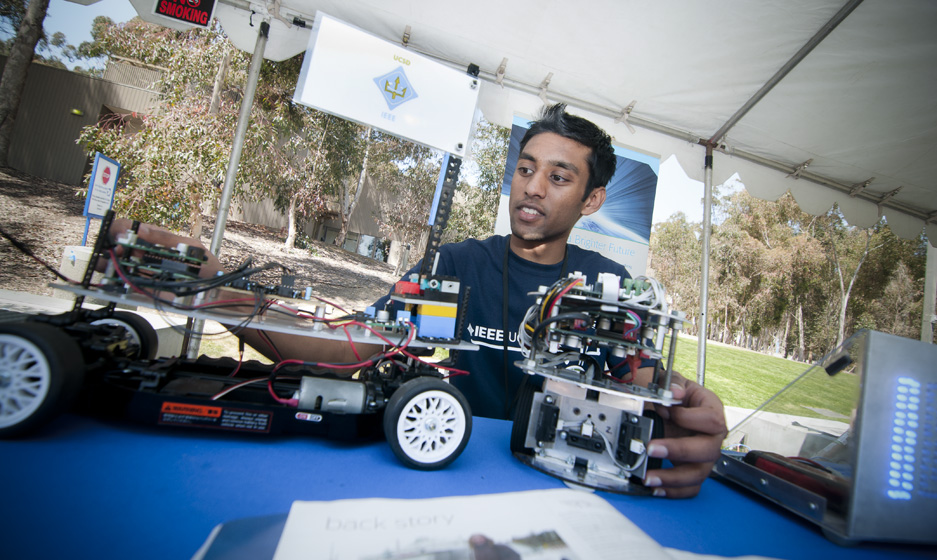 Vikram Bhasker, from the UCSD student organization IEEE, shows off a vehicle powered by electric current.