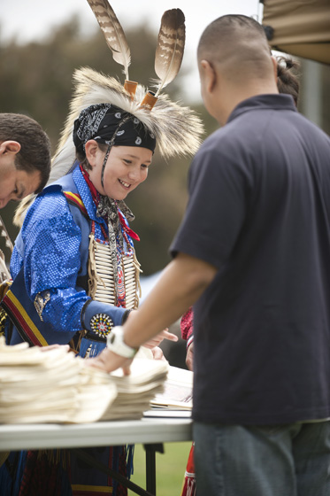 Head Boy Dancer, Baltazaar Jackson of the Lipan Apache-People of the Tall Grass Clan/Mescalero looks though the vendor booths during the powwow.