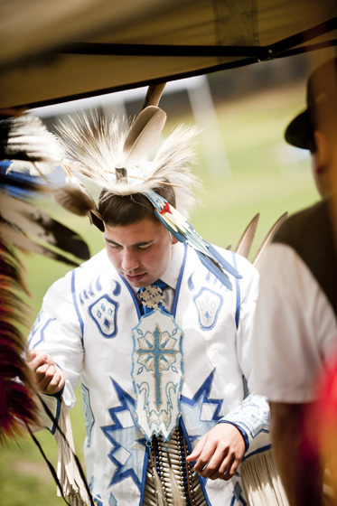 A Kumeyaay dancer gets dressed in his regalia for the powwow.