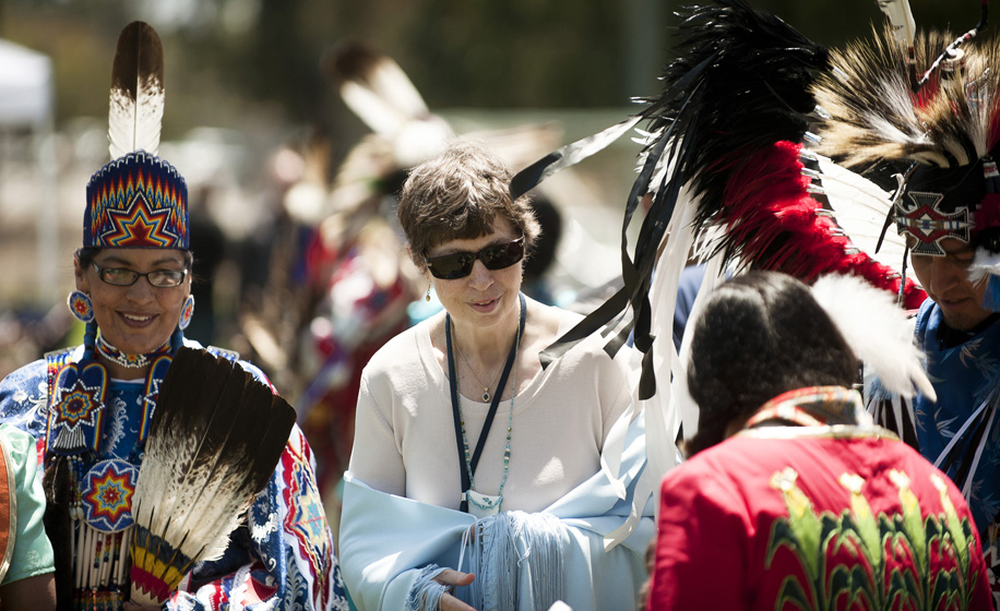 Powwow attendees greet Chancellor Marye Anne Fox during a walk around the dancing arena.
