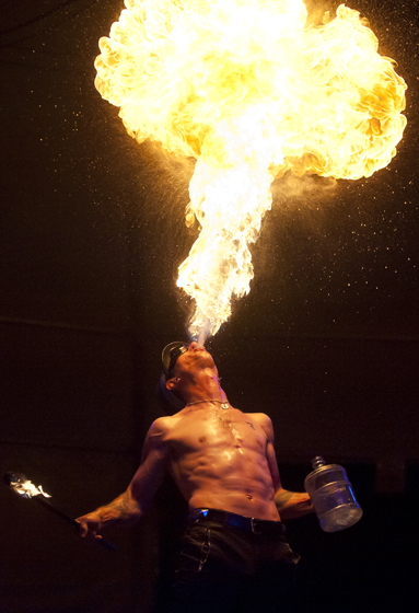 A Cirque Berzerk firebreather illuminates the Midway Tent during Sun God Festival.