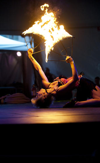 A Cirque Berzerk performer dances with fire in the Midway Tent.