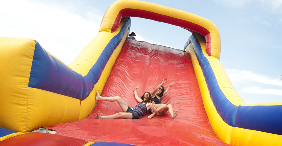 Students slide down a giant inflatable slide and obstacle course featured at Sun God.