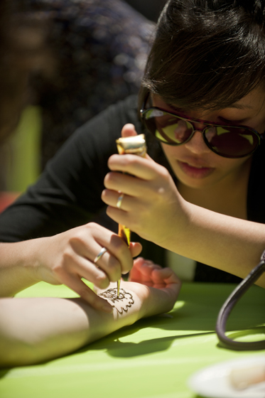 A Revelle student receives a henna-adorned wrist painting.