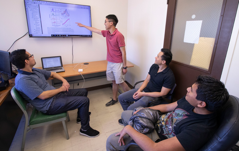 "Graduate student Matthew Du points to the ""pink line,"" indicating exciting results from the study. His colleagues Raphael Ribeiro (left), Joel Yuen-Zhou (top right) and Luis Martínez-Martínez look on. Photo by Michelle Fredricks, UC San Diego Physical Sciences"