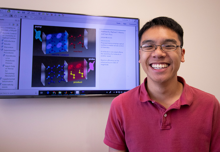 Matthew Du pictured if front of a presentation slide displaying the theoretical model of the two optical cavities. Photo by Michelle Fredricks, UC San Diego Physical Sciences