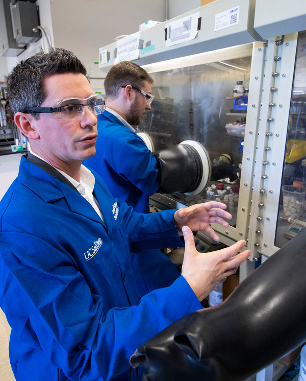 Professor Joshua Figuroa (lower left) describes the experiment he and Myles Drance successfully completed. Drance works in the glovebox in the background. Photo by Michelle Fredricks, UC San Diego Physical Sciences
