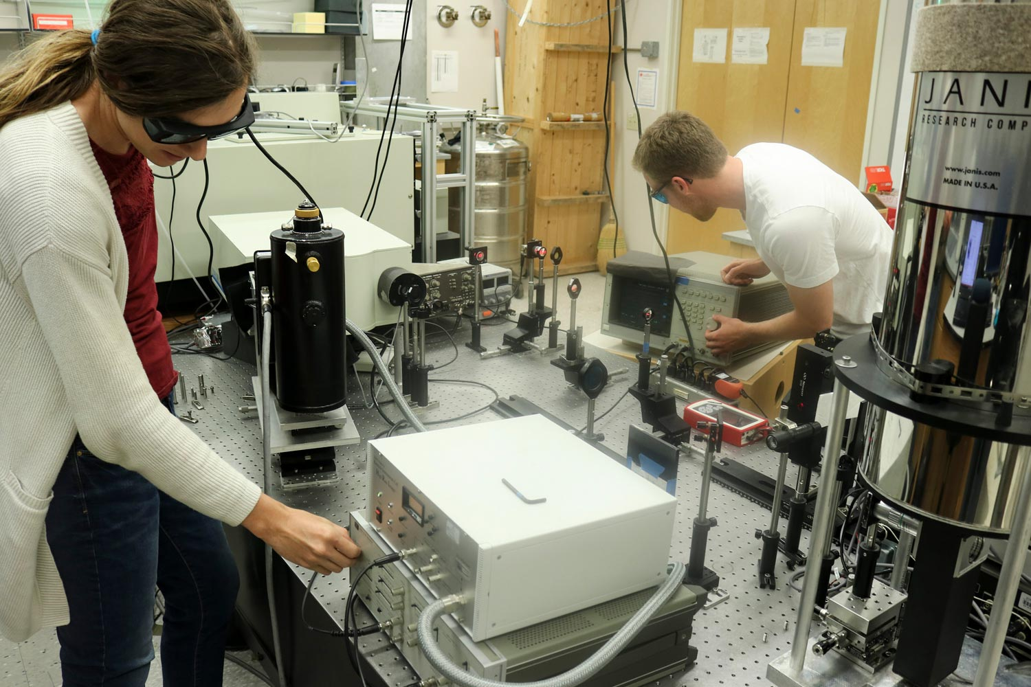 Ph.D. candidates Erica Calman and Lewis Fowler-Gerace adjust the electronics and optics used for the experiment