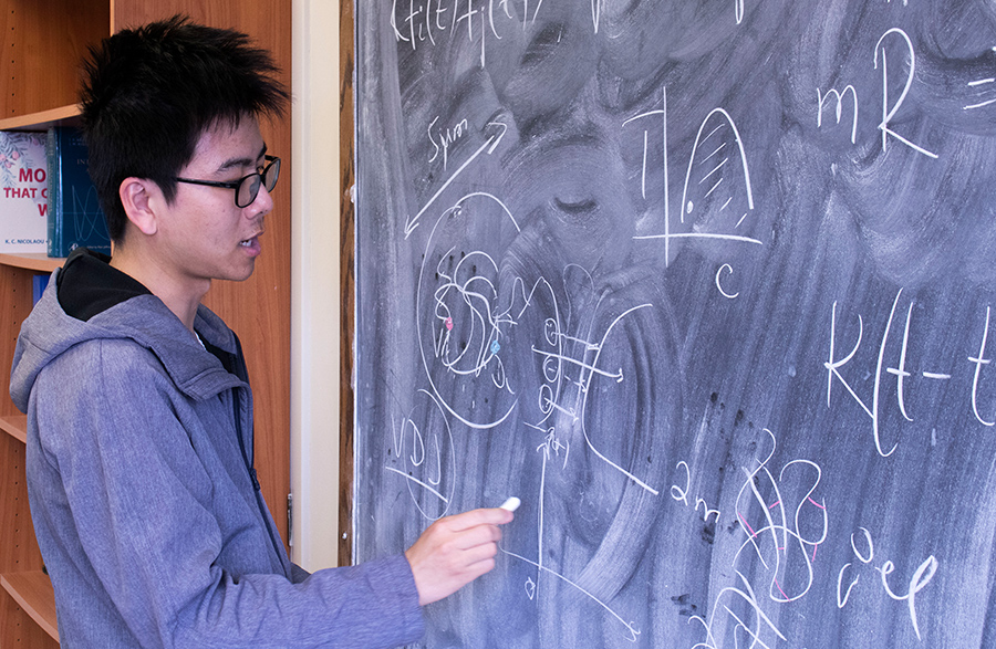 Physics graduate student Bin Wang, who works with Dudko, charts temporal and spatial aspects of the research. Photo by Michelle Fredricks, UC San Diego Physical Sciences