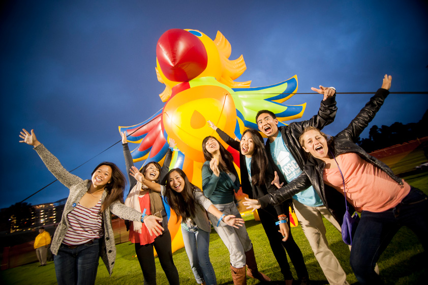 Students pose for photos in front of the inflatable Sun God at the All Campus Graduation Celebration.