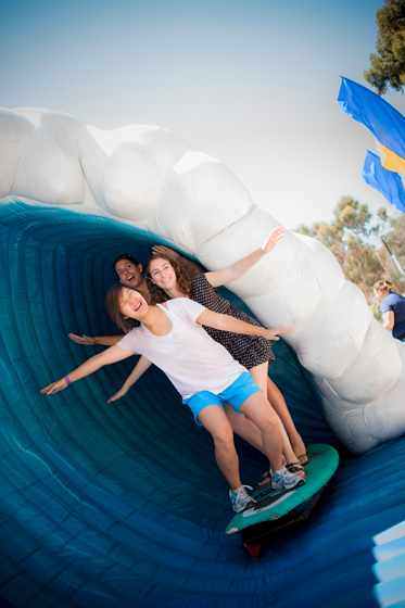 Participants pose for photos on an inflatable wave near the staff alumni booth.