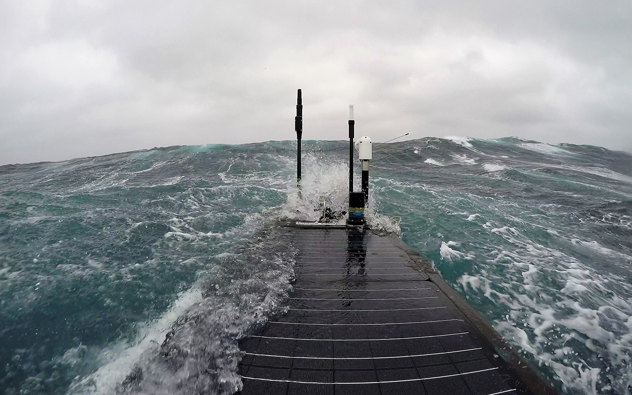 An instrument platform called a Wave Glider floats through ocean swells as it gathers data