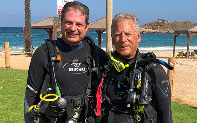 Two archaeologists side by side in diving gear on Mediterranean beach prior to underwater survey of ancient site near Akko in Israel