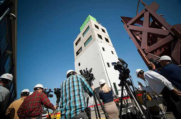 Image: Reporters prepare to record a test on a five-story building equipped with a wide range of non-structural components, such as an elevator and sprinklers, at the UC San Diego shake table in April 2012.