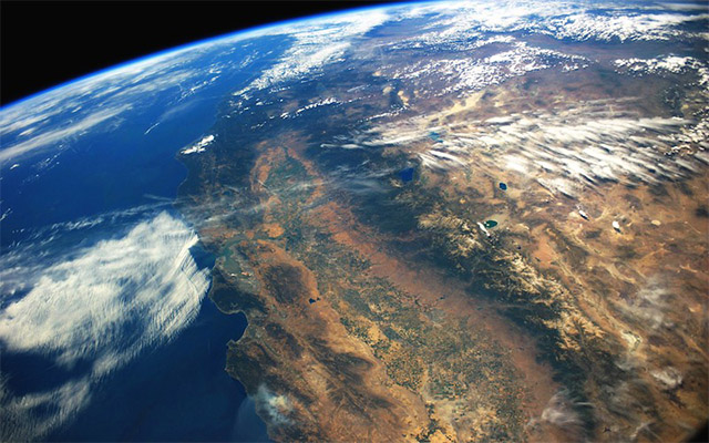 An image of California's Central Valley as seen from the International Space Station. The curve of Earth is visible against a dark sky.
