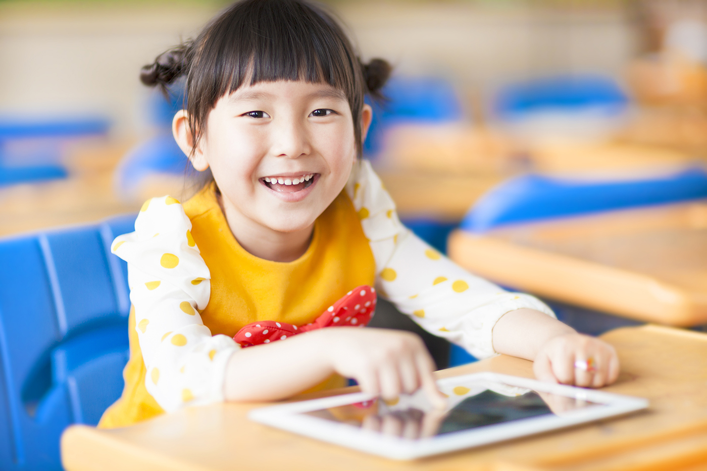 Happy girl on tablet - photo by iStock/Tomwang112