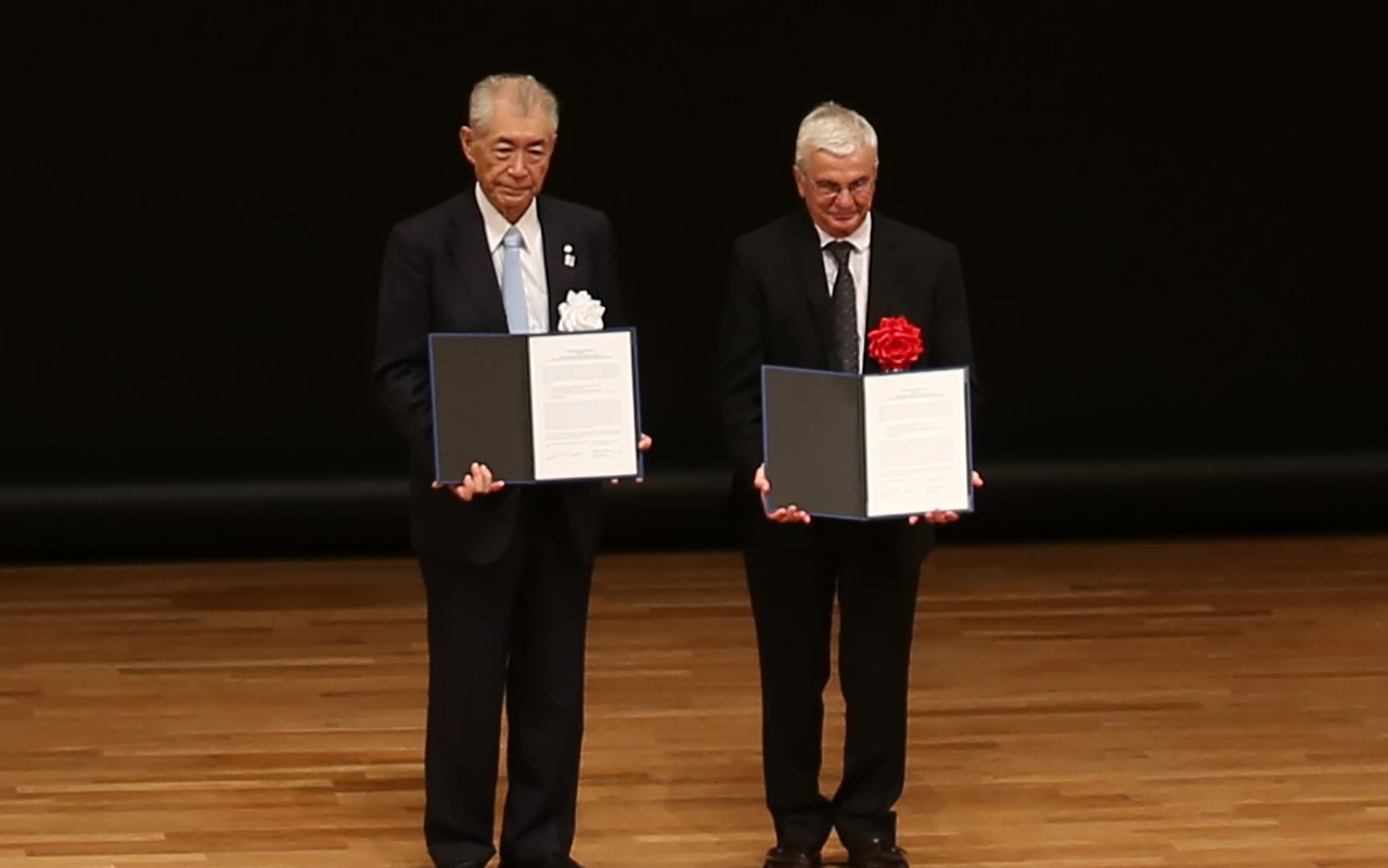 FBRI President Tasuku Honjo and Distinguished Professor of Pathology Napoleone Ferrera hold signed copies of the MOU.