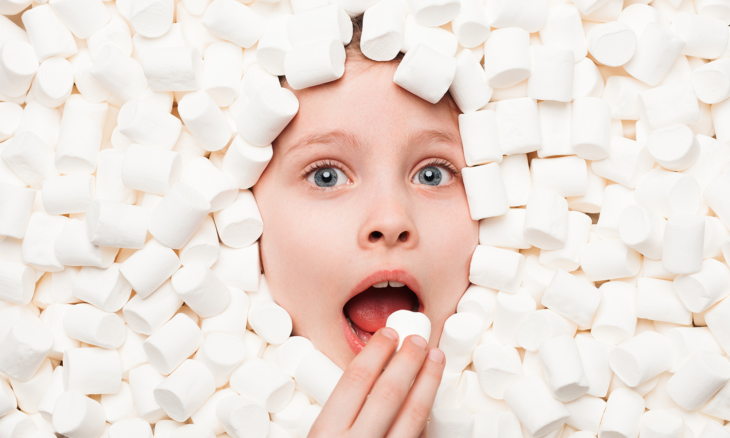 Child surrounded by marshmallows about to eat a marshmallow