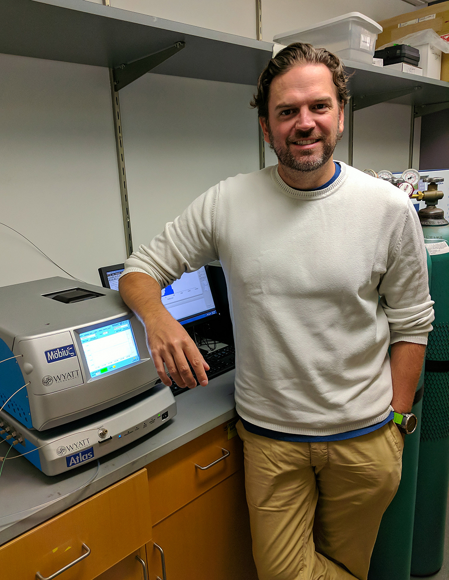 Researcher poses in front of lab equipment