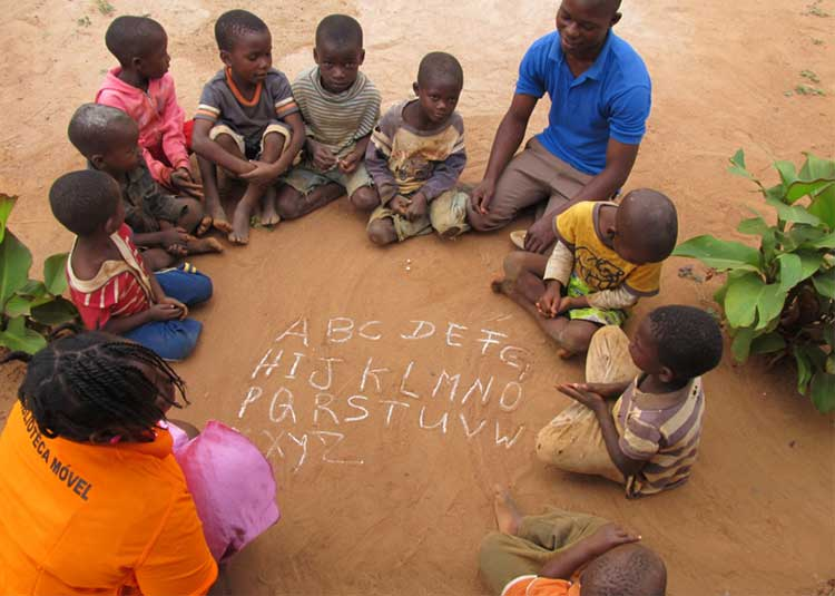 Image: Two Peace Corps volunteers practicing the alphabet with children in Mozambique