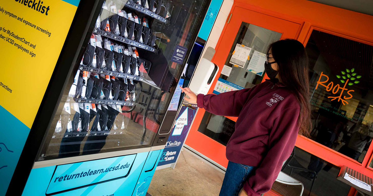 UC San Diego student retrieving a COVID test from a campus vending machine