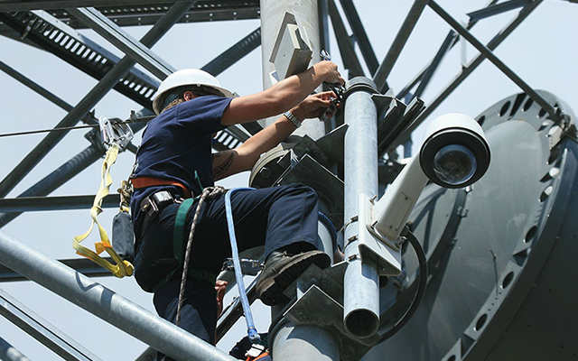 An engineer installs an antenna on a microwave tower to connect a nearby fire station to HPWREN.
