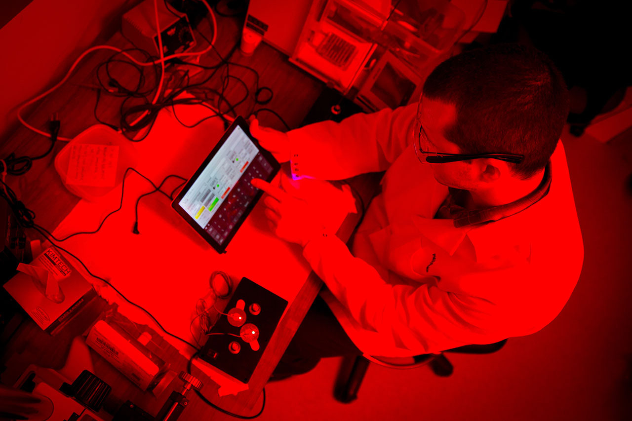 Postdoctoral researcher and first author Phillip Kyriakakis demonstrates the desktop system powered by the new optogenetic switch researchers developed.