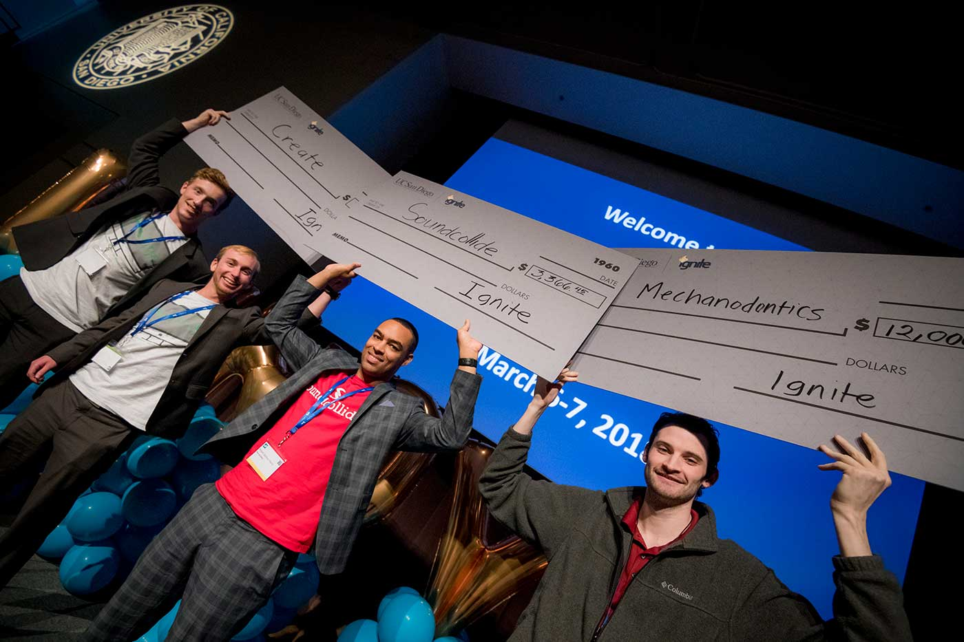 winners holding giant checks
