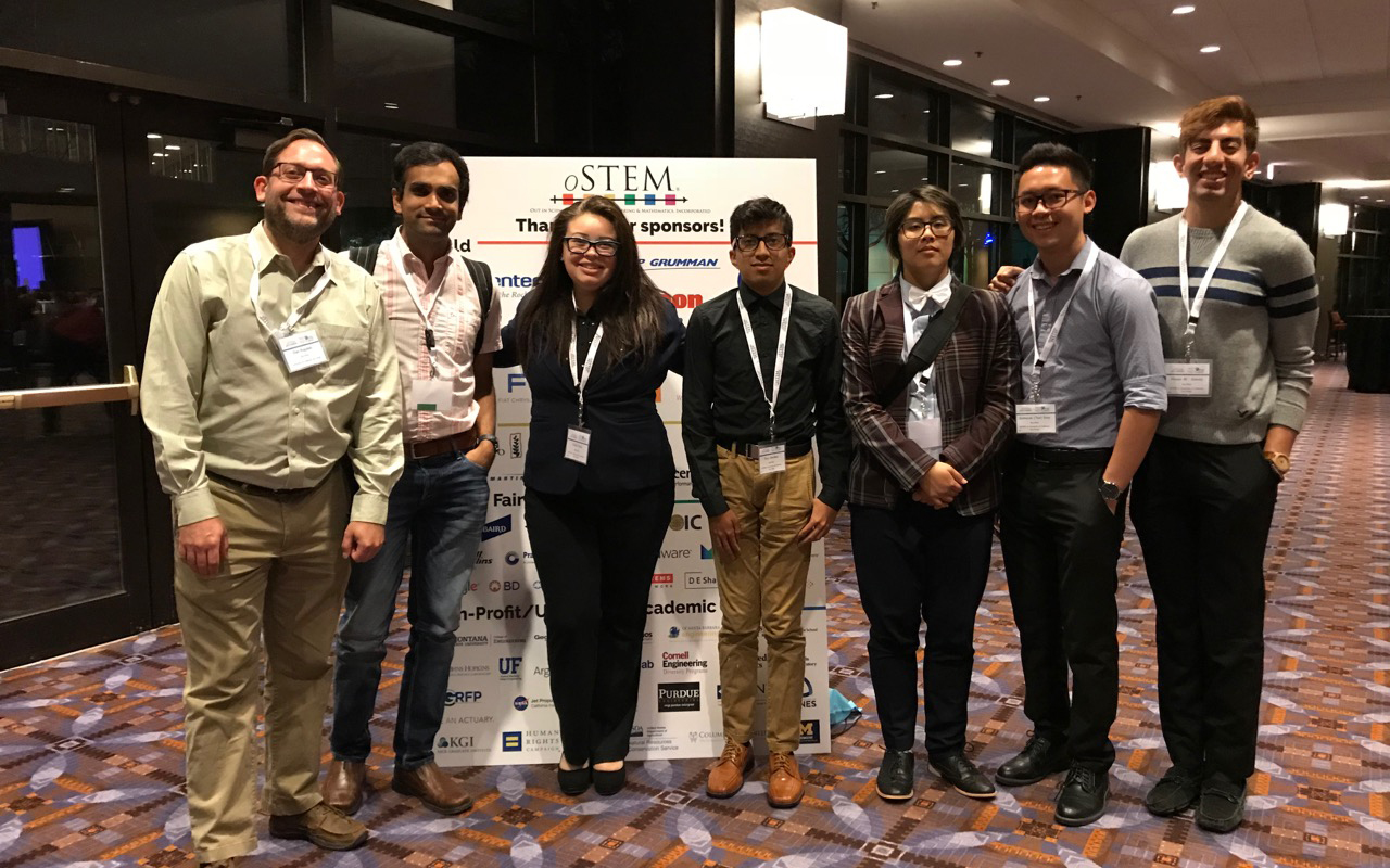 Photo of two professors at left and at right five undergraduate students in front of a sign for oSTEM conference they attended.