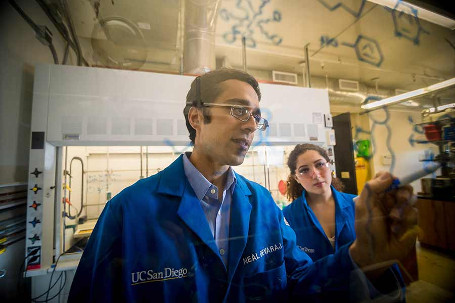Professor Neal Devaraj with a student at the research lab