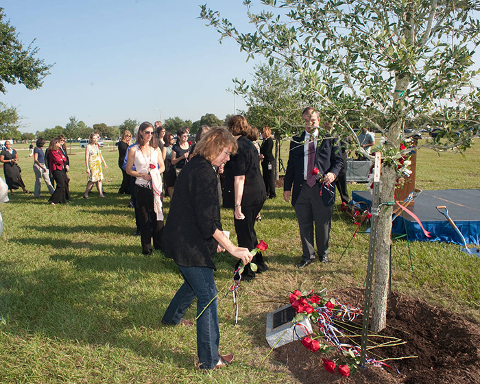 astronaut Sandra Magnus places a rose at a tree planted in Sally's memory.