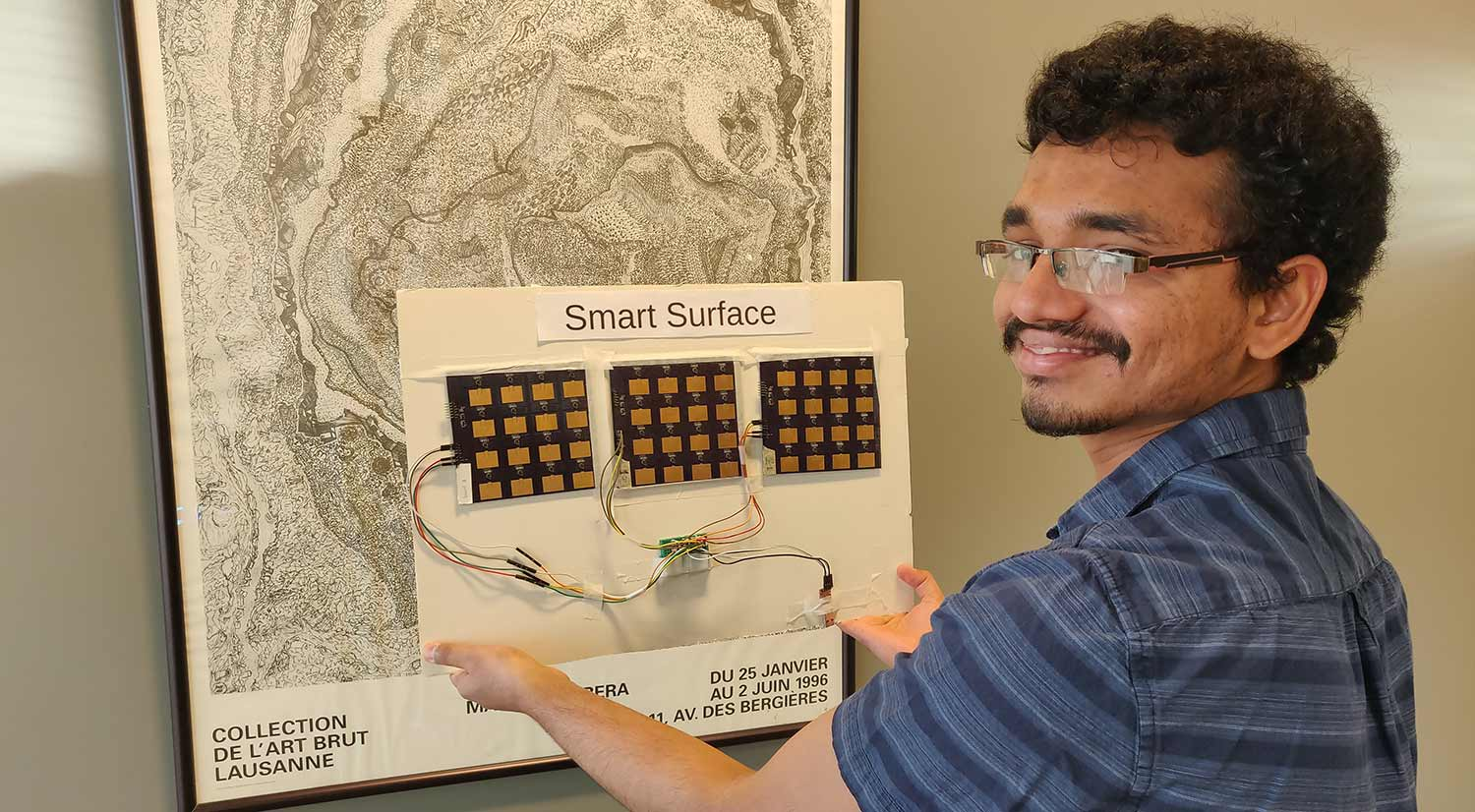 "Student holds a WiFi-boosting ""smart surface"" (made of printed circuit boards) up against a wall."