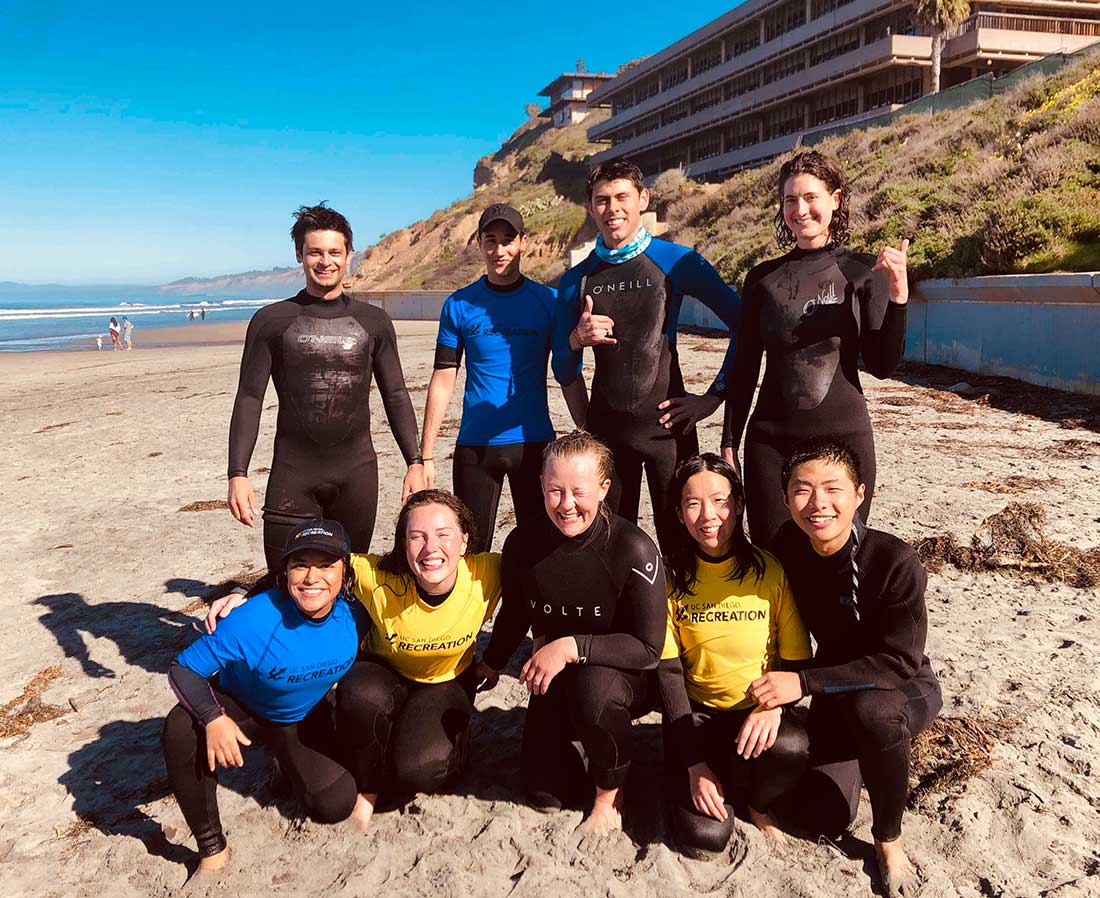 Francesca Hart on the beach with surfing students.