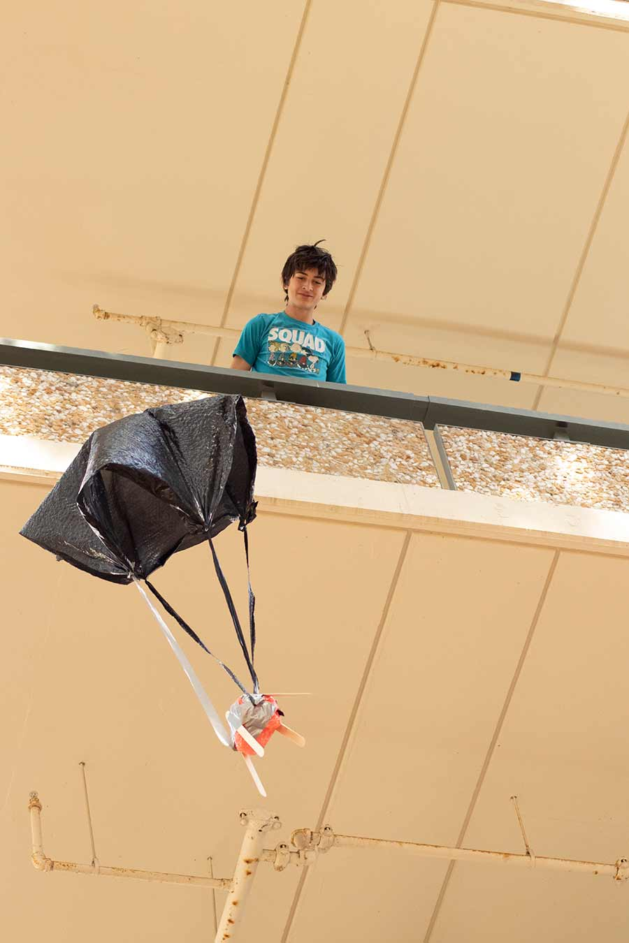 student dropping egg parachute
