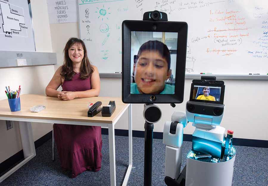 UC Irvine researcher Veronica Newhart with two of the telepresence robots.