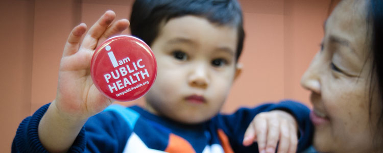 Toddler holding I am Public Health pin