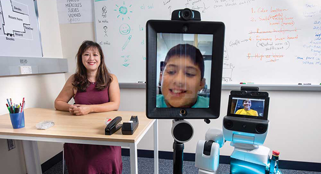 UC Irvine researcher Veronica Newhartwith two of the telepresence robots.