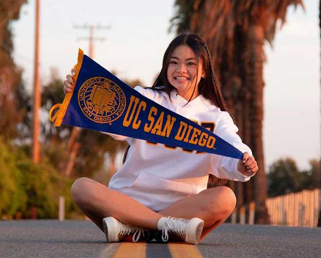 student with UC San Diego flag.